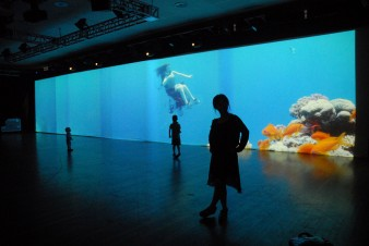 Long panoramic video installation from floor to ceiling and the length of the large darkened room showing a tropical underwater environment with a woman scuba diving in a wheelchair. Silhouettes of two children and a woman watching the projection stand, s