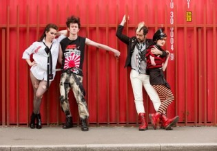 photo of a group of four punks posing in line against a red fence