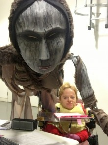 photo of Sophie Partridge looking from beneath the armpit of the large puppet Semmersauq