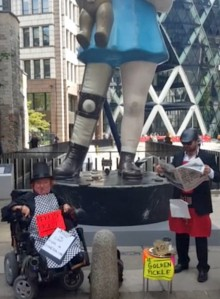 photo of artists Katherine Araniello and Simon Raven dressed in black costumes with a stall of 'golden pickles'  pictured in front of the Damien Hirst 'Charity' sculpture near the Gherkin