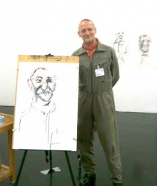 photo of poet Vince Laws standing in front of an easel with a sketch by tanya raabe